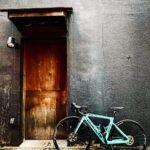 """<span class=""""title"""">壁シリーズ。黒い壁。 居酒屋🏮さんの出入り口。木のドア🚪の色褪せ具合がいい味出してました。  早く思い切り飲みに行けるといいなぁ〜〜🍺  #ビアンキ #ビアンキ女子 #ビアンキ女子っぽくない写真 #ビアンキと黒い壁 #ロードバイクのある風景 .. #ロードバイクJP</span>"""
